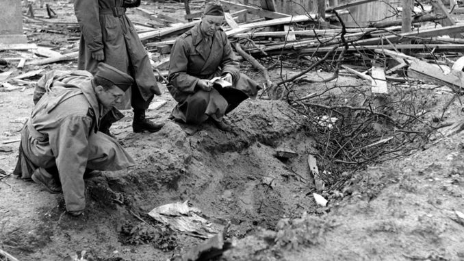 Not published in LIFE. LIFE correspondent Percy Knauth, left, sifts through debris in the shallow trench in the garden of the Reich Chancellery where, Knauth was told, the bodies of Hitler and Eva Braun were burned after their suicides.