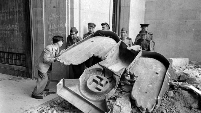 Not published in LIFE. Russian soldiers and a civilian struggle to move a large bronze Nazi Party eagle that once loomed over a doorway of the Reich Chancellery, Berlin, 1945.