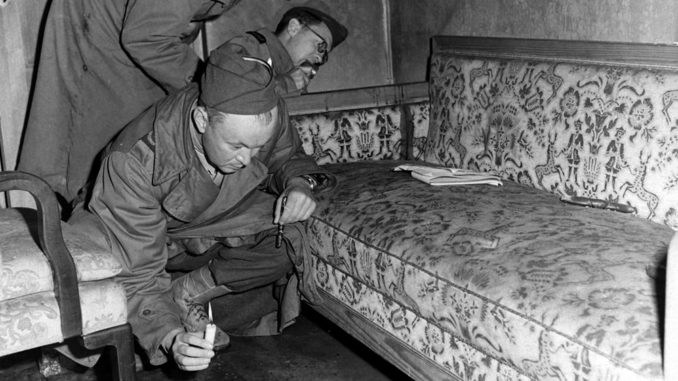 With only candles to light their way, war correspondents examine a couch stained with blood (see dark patch on the arm of the sofa) located inside Hitler's bunker.